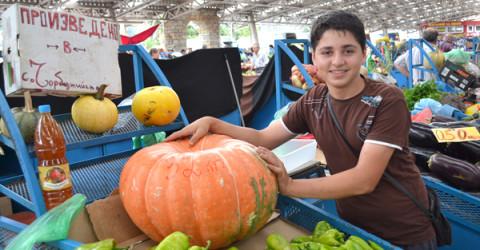 14-годишният Мехмед Али с гордост позира пред отгледаната от него 32- килограмова тиква на пазара в Кърджали.
